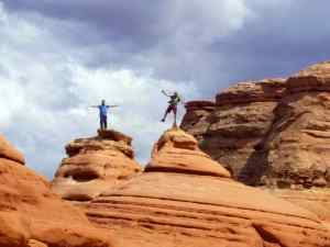 KC and Brian balancing on top of rock formations near the Delicate Arch