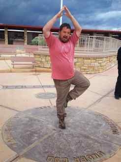 KC doing a tree pose on the four corners survey monument
