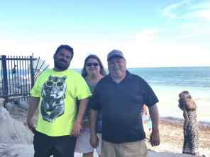 KC poses for picture with his parents on a beach in Florida